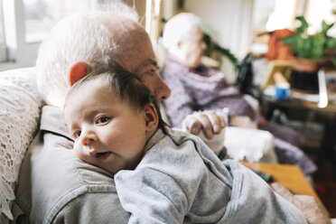 Great-grandfather holding baby at home with his wife in background - GEMF01519