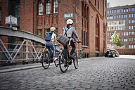 Germany, Hamburg, back view of couple riding electric bicycles at Old Warehouse District - RORF00640