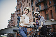 Germany, Hamburg, Old Warehouse District, couple with electric bicycles wat ching something - RORF00643