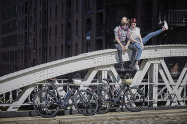 Germany, Hamburg, couple with electric bicycles sitting on railing of a bridge - RORF00649