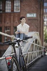 Germany, Hamburg, electric bicycle leaning against railing on a bridge - RORF00655