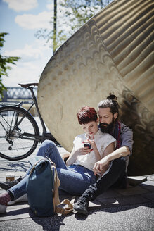 Germany, Hamburg, couple on bicycle trip having a rest looking at cell phone - RORF00658