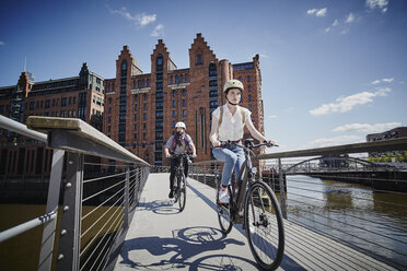 Germany, Hamburg, couple riding electric bicycles on bridge at Old Warehouse District - ROR00667