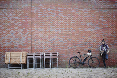 Man with electric bicycle leaning against brick wall looking at cell phone - RORF00673