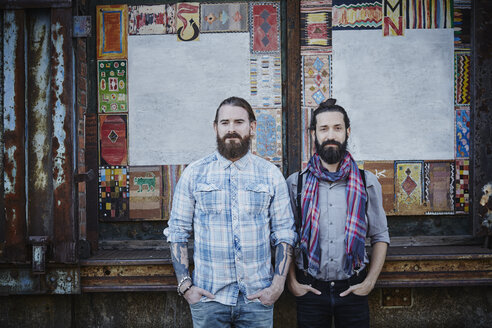 Portrait of two bearded friends standing side by side with hands in their pockets - RORF00676