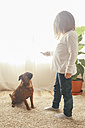 Little girl training her dog to sit at home - RTBF00697