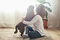 Little girl sitting on the carpet hugging her dog - RTBF00700