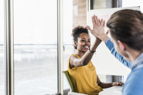 Happy young woman high fiving with colleague in office - UUF10009