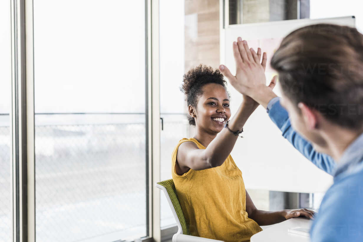 Happy young woman high fiving with colleague in office - UUF10009 - Uwe Umstätter/Westend61
