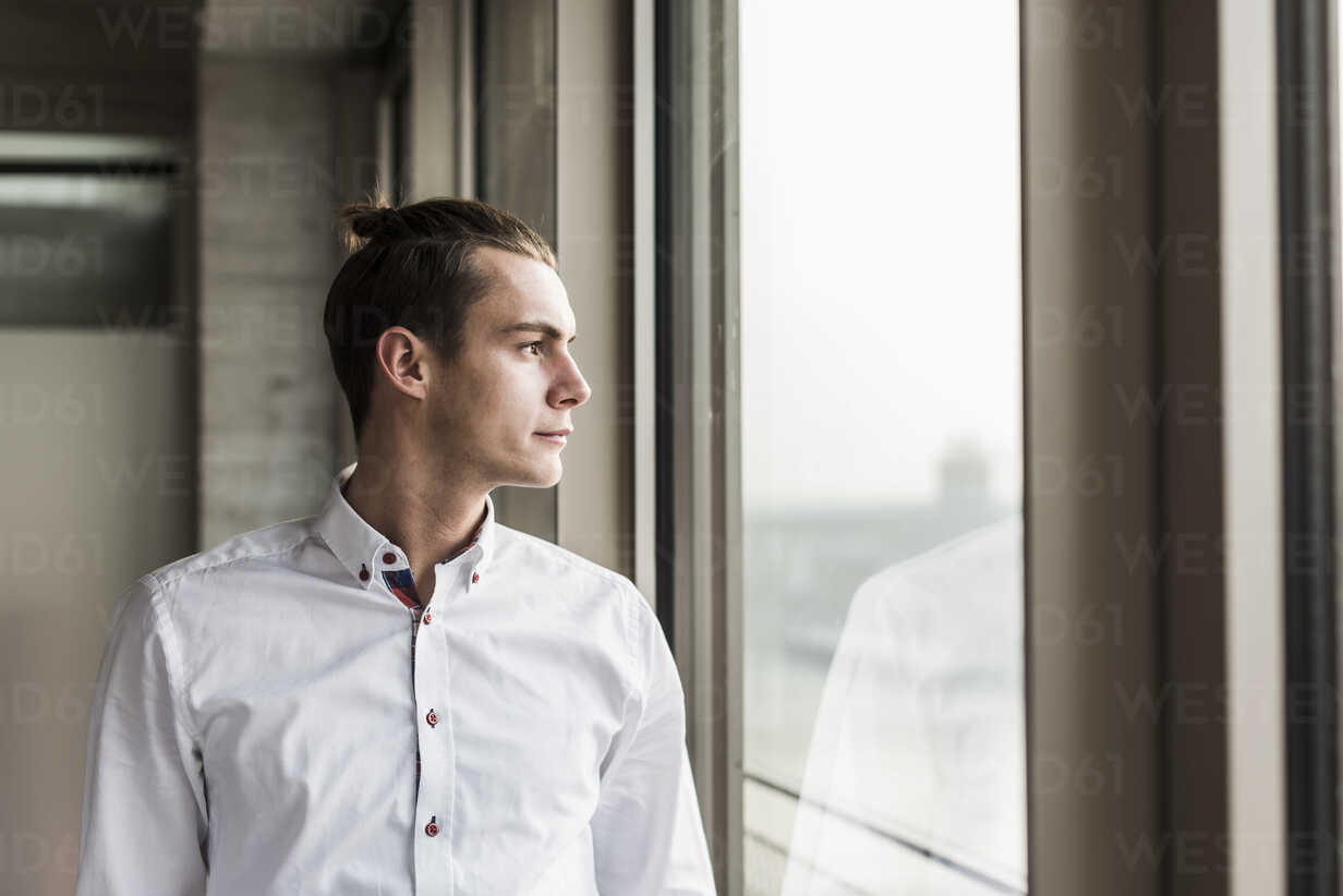 Young businessman looking out of window - UUF10051 - Uwe Umstätter/Westend61