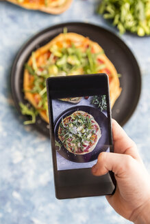 Hand of girl taking picture of homemade vegetarian pizza with cell phone, close-up - SARF03218