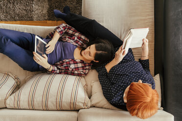 Adult daughter using tablet and mother reading book at home - ZEDF00530