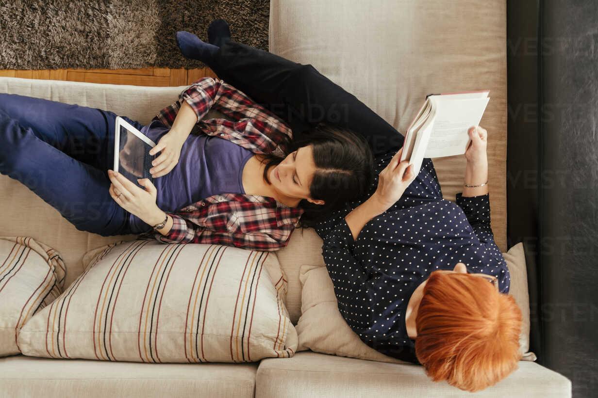Adult daughter using tablet and mother reading book at home - ZEDF00530 - Zeljko Dangubic/Westend61