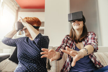 Adult daughter with mother at home wearing VR glasses - ZEDF00533