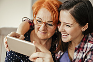 Happy adult daughter with mother taking a selfie - ZEDF00539