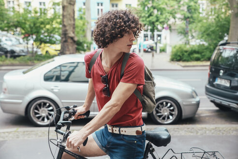 Young man riding bicycle on pavement turning around - RTBF00703