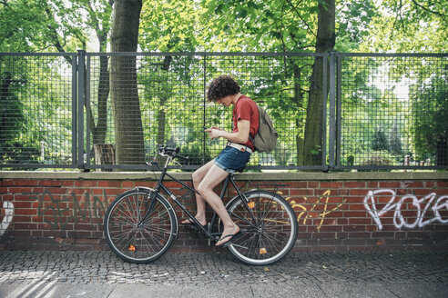 Young man using cell phone sitting on his bicycle - RTBF00709