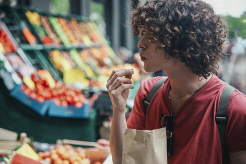 Young man eating cherries in front of street fruit stand - RTBF00718