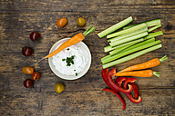 Bowl of herb yoghurt dip, cherry tomatoes and various vegetable sticks on wood - LVF05920