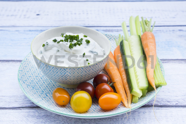 Bowl of herb yoghurt dip, cherry tomatoes and vegetable sticks on plate - LVF05923