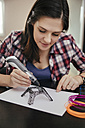 Young woman drawing Eiffel Tower with 3D pen - ZEDF00543
