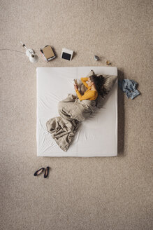 Woman lying in bed reading a book, top view - JOSF00613