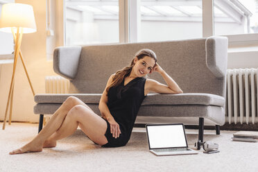Portrait of smiling woman leaning on couch next to laptop - JOSF00622