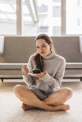 Portrait of woman sitting on floor eating piece of cake - JOSF00625