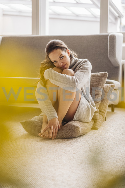 Portrait of woman sitting on cushion on floor - JOSF00637