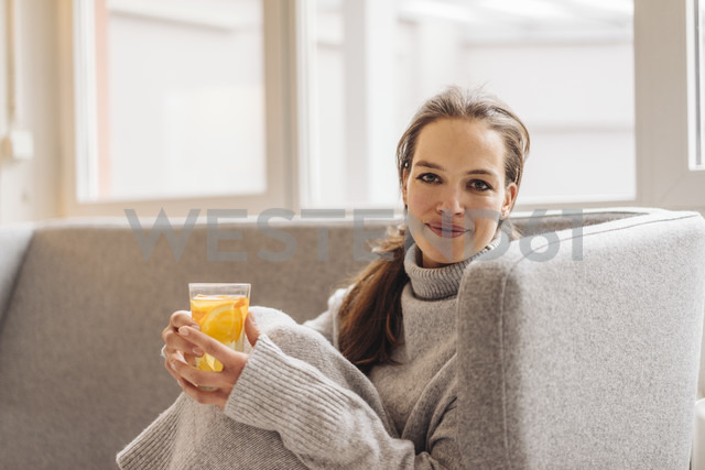 Portrait of woman sitting on couch holding fresh drink - JOSF00643