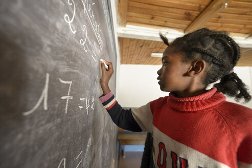 Madagaskar, Girl in Fianarantsoa elementary school calculatiing at blackboard - FLKF00757