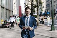 Handsome businessman walking in Manhattan, carrying digital tablet - GIOF02049