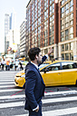 Businessman in the streets of Manhattan hailing a cab - GIOF02070