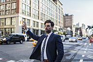 Businessman in the streets of Manhattan hailing a cab - GIOF02073