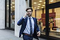 Handsone businessman in a hurry running through Manhattan, using smart phone - GIOF02094