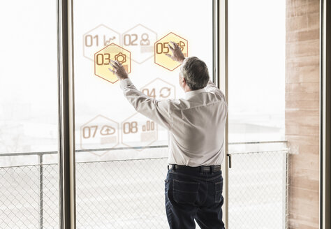 Businessman touching windowpane with data in office - UUF10056