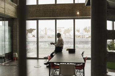 Businessman looking at windowpane with world map and data in office - UUF10062
