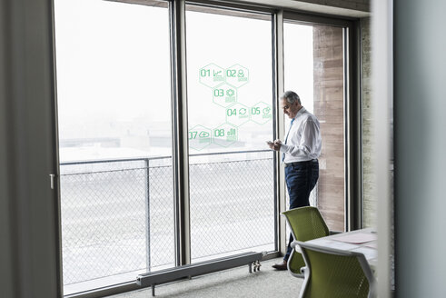 Businessman standing at windowpane with data in office - UUF10065