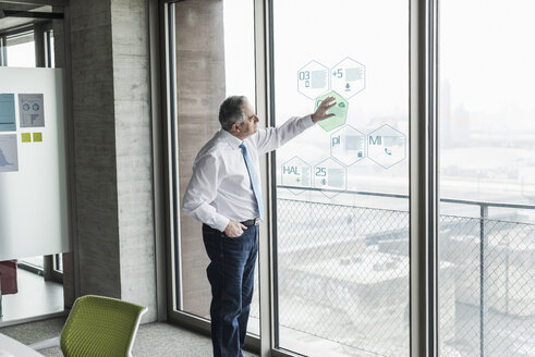 Businessman touching windowpane with data in office - UUF10068