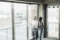 Businessman and woman at windowpane with data in office - UUF10071
