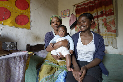 Madagascar, Fianarantsoa, Baby boy, mother and grandmother sitting in livingroom - FLKF00761