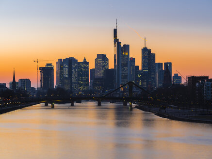 Germany, Frankfurt, view to skyline with Floesserbruecke and Main River in the foreground at twilight - AMF05300