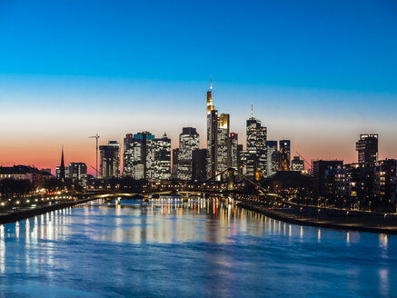 Germany, Frankfurt, view to skyline with Floesserbruecke and Main River in the foreground at twilight - AMF05303