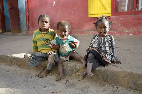 Madagaskar, Fianarantsoa, Homeless children sitting on pavement - FLKF00768