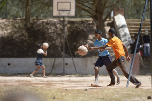 Madagascar, Fianarantsoa, Boy playing soccer in school yard - FLKF00777