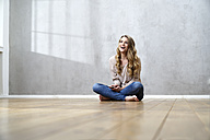 Laughing blond woman sitting on the floor with cell phone - FMKF03567