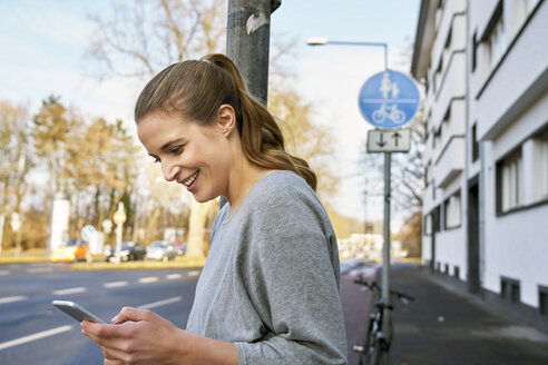 Smiling blond woman looking at cell phone - FMKF03573
