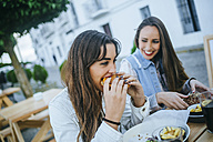 Two women eating Hamburgers in a street restaurant - KIJF01303
