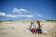 Two young women with ukulele sitting on blanket on the beach - KIJF01306