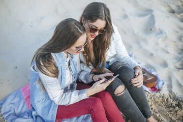 Two young women sitting on the beach looking at cell phone - KIJF01309